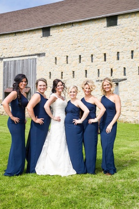 Bride with bridesmaids in one shoulder long blue bridesmaid dresses