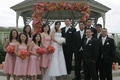 Bride in a Vera Wang gown with groom and groomsmen in black tuxedos, and bridesmaids in pink dresses