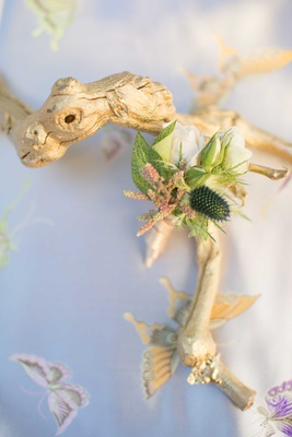 gold leaf driftwood on blue table linen with butterflies and small green boutonniere