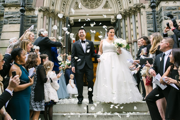 wedding ceremony at catholic church bride and groom on stairs with flower petals getaway car