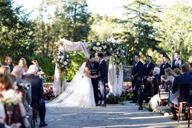 outdoor wedding ceremony arch with drapery and flowers greenery bride and groom stone aisle ohio