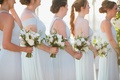 bridesmaids with low buns ivory flower bouquets sunset ocean view ceremony