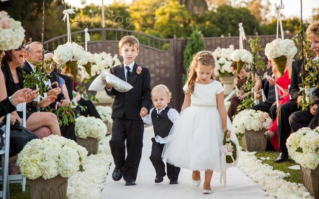 Three children walk down petal-lined aisle