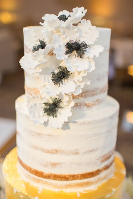 Wedding cake with gold bottom tier and nearly naket top tiers with sugar flower anemone blooms