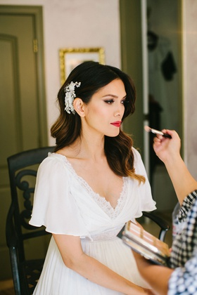 bride in v neck wedding dress with flutter sleeves glamorous curls headpiece red lipstick makeup