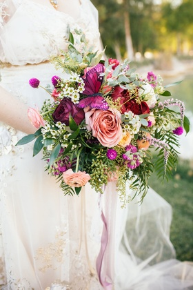 Bridal bouquet of greenery peach and red roses, light orange ranunculus, crimson peony, butterfly