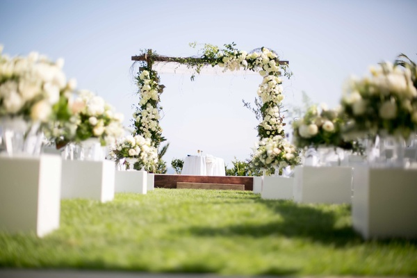 wooden chuppah white green florals seaside ceremony arrangements down aisle jewish wedding