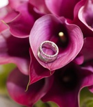 Wedding rings on purple calla lily bouquet