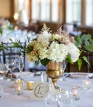 low eclectic floral arrangement gold vessel white pink flowers green leaves candles