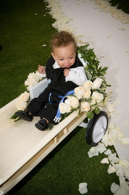 Young ring bearer in white wagon at wedding ceremony