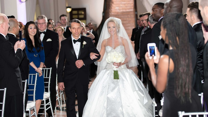 Bride on arm of father of the bride in tuxedo wearing Ines Di Santo ball gown
