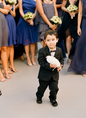 Little boy in dark suit with bow tie and ring pillow
