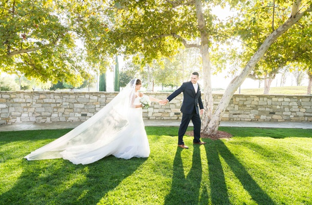 groom leads bride outside park setting catholic wedding california garden black suit long veil
