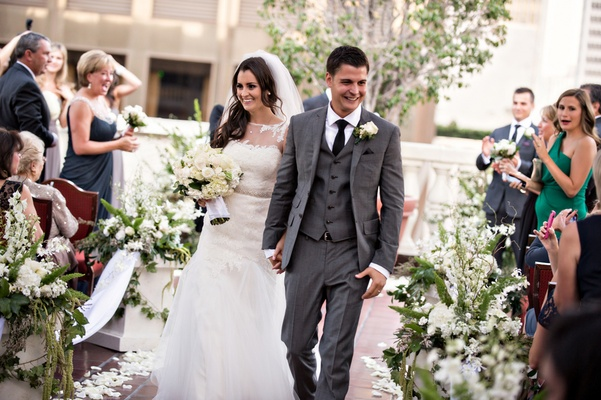 newlyweds walk down aisle lined with white flowers and greenery
