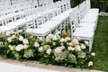 White wedding ceremony chairs on grass lawn for outdoor nuptials green leaves, pink white roses