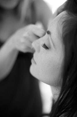 Black and white photo of bride getting makeup done