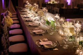 Purple lighting at wedding reception grey linen head table with white low flower arrangements candle