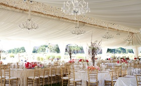 Wedding tent reception with crystal chandeliers, pink flower arrangements, and golden chairs