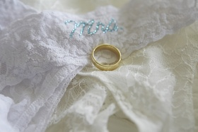 Gold wedding band on top of lace intimate garments