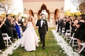 bride in pretty hayley paige wedding dress holding groom's hand walking down grass aisle flowers
