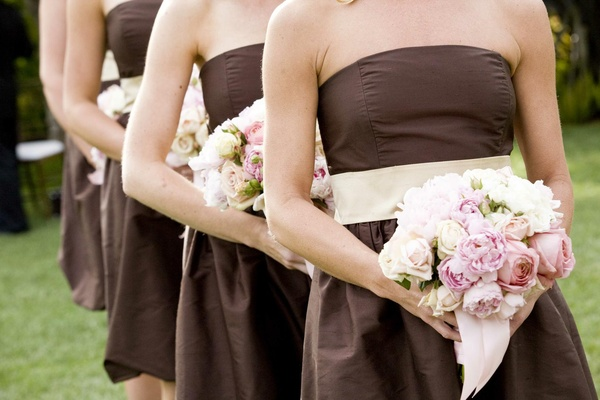 Bridesmaids in brown dresses hold pink peony bouquets