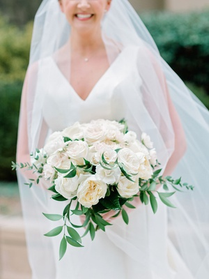 bride in v neck wedding dress sareh nouri holding white rose bouquet greenery