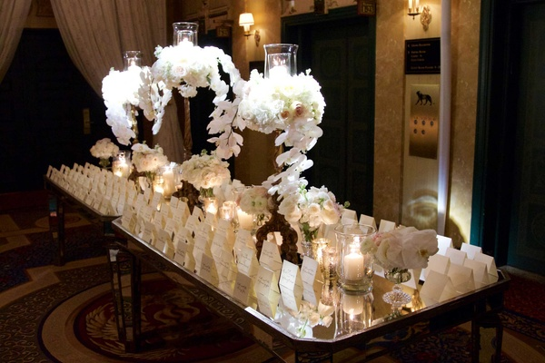 Long mirror tables with escort cards white and tall arrangements of orchid hydrangea flowers