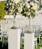 Crystal riser with greenery, white hydrangea, rose in white pink white riser white chairs ceremony