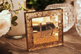mosaic confetti table number gold metallic mirror reflecting candlelight