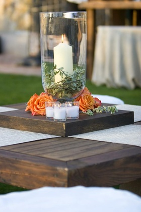 Hurricane vase with candle, leaves, and orange rose