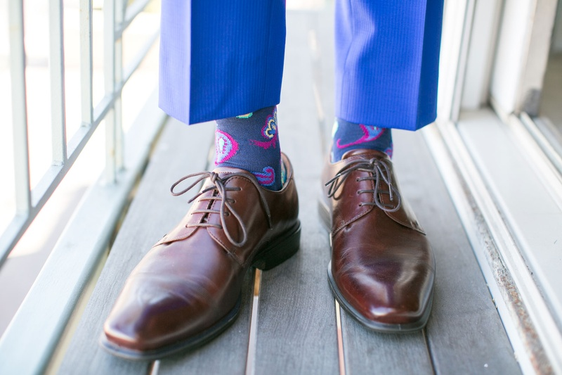 grooms brown shoes with blue pants and silly socks