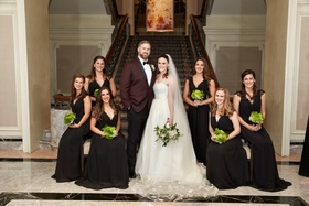 Bride with groom in burgundy suit with bridesmaids in black cap sleeve dresses green bouquets