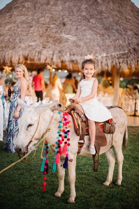 Mexico wedding welcome party little girl on donkey with saddle and necklace pom poms on