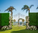 wrought iron gate ceremony couples initials florals white pink greenery beach hotel del coronado