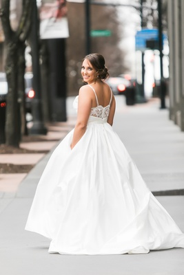 bride in modern trousseau ball gown with lace back, spaghetti straps, and pockets