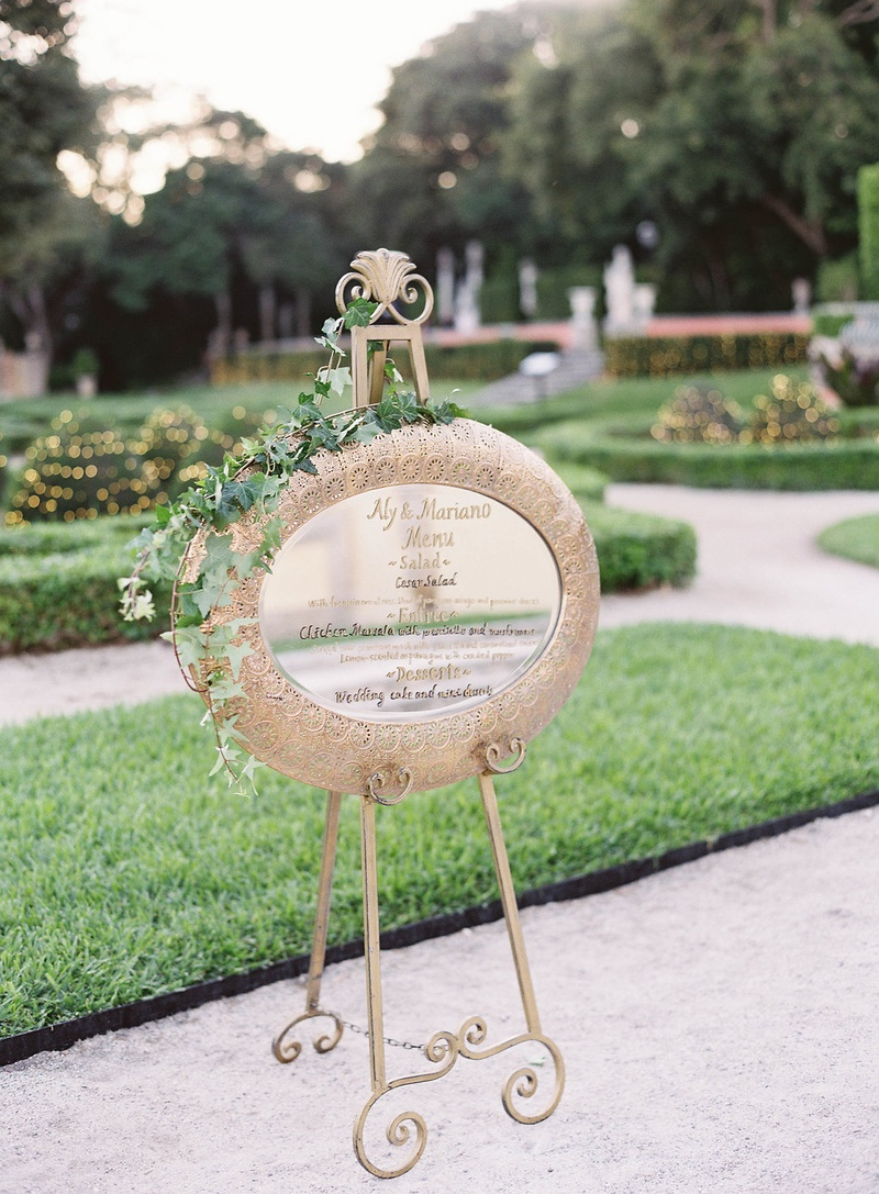 easel with gold framed mirror gold calligraphy menu greenery vines decorated garden