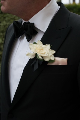 Ivory gardenia boutonniere on groom lapel pocket square bow tie tuxedo