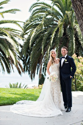 Bride in Ines Di Santo lace wedding dress long train and veil soft bouquet blonde hair groom in tux