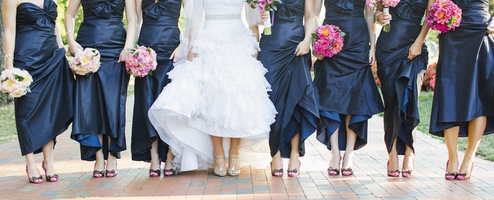 Bride and bridesmaids pulling up dresses