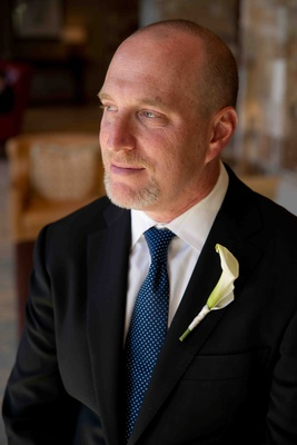 Groom with blue tie and white calla lily boutonniere