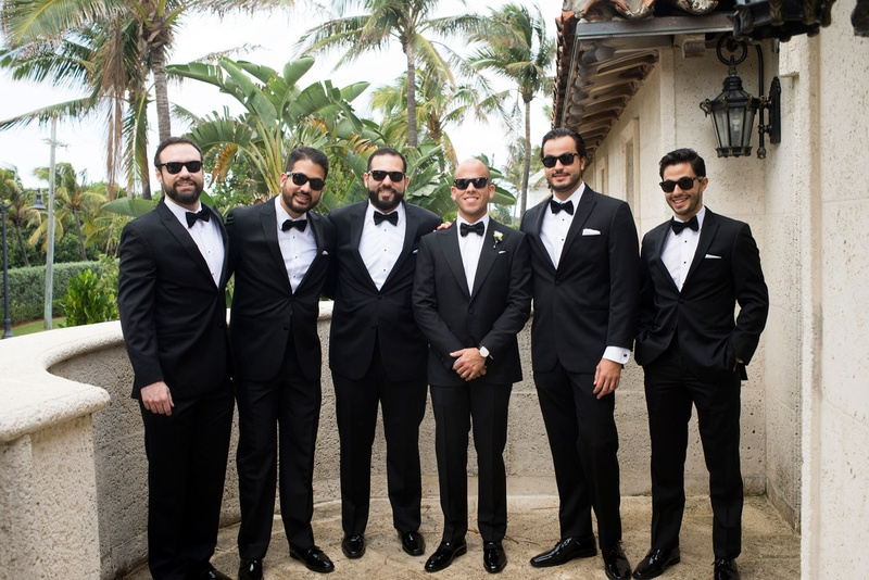 Groom in sunglasses and bow tie tuxedo with groomsmen in matching outfits on balcony