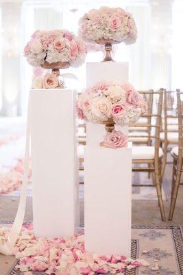 wedding ceremony entrance white risers with pink white rose flowers in gold footed vases flowers