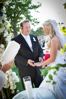 Bride in a Pnina Tornai gown and veil exchanges vows with groom in black tuxedo and white bow tie