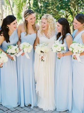 Bride in lace wedding dress with bridesmaids in long light pastel blue bridesmaid dresses