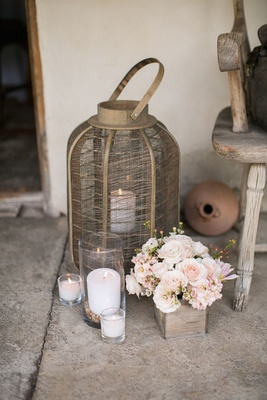 Ranch wedding reception with mesh metal lantern, candles in glass vessels, pink roses in wood box