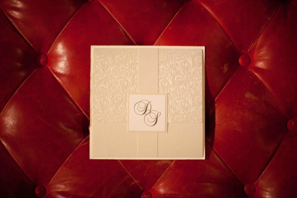 Cream invitation front with monogram on red tufted background