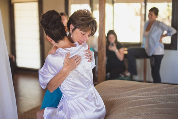 Bride with high bun silk bride robe hugs mother of bride before the wedding ceremony