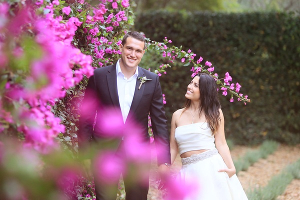 bride in monique lhuillier crop top wedding dress, smiles with groom in armani