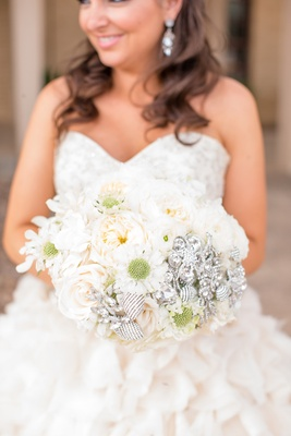 Bride in ruffle wedding dress holding white bouquet with brooches