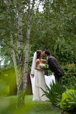 Bride in a Claire Pettibone gown kisses groom in a garden